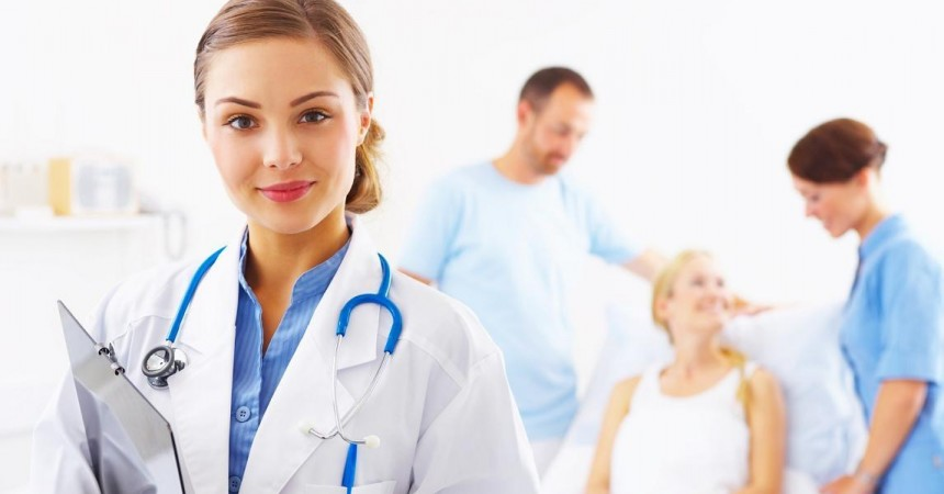 Portrait of a doctor with two of her co-workers talking with a patient in the background